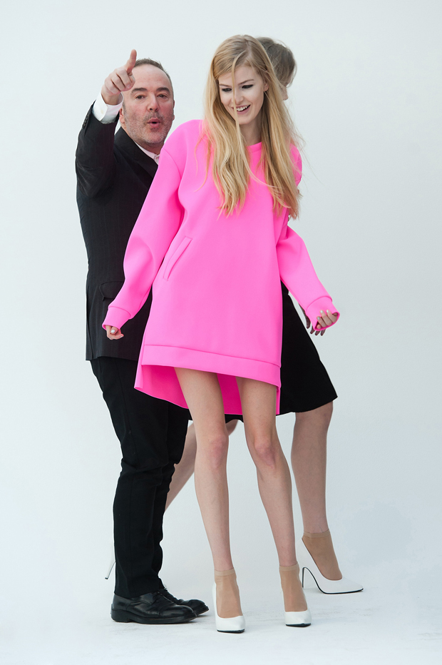 John Patrick in a tux with a blonde model in a hot pink sleeved dress