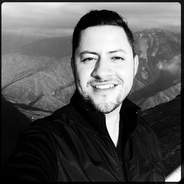Mario Estrada takes a black and white selfie in front of a canyon backdrop