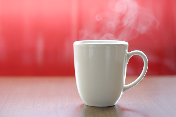 coffee in a white porcelain cup against a red background