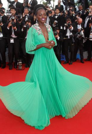 Lupita Nyong'o wearing a jade green pleated dress.