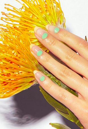 A mint green and lemon yellow negative space manicure.