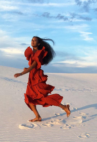 Solange Knowles wearing a red dress and running in the sand.