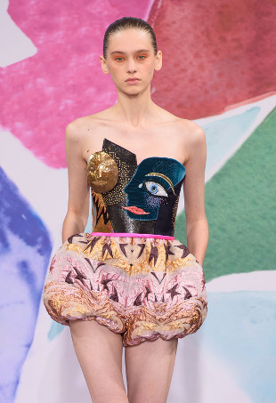 A model wearing a face print bustier and pink ruffled shorts from Schiaparelli Fall 2016 Haute Couture