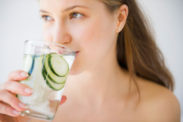 A beautiful girl drinking cucumber water