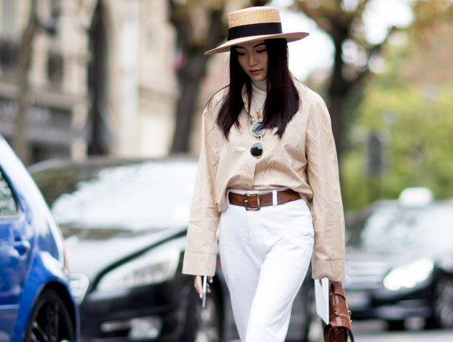 A showgoer at Paris Fashion Week wears a straw boater hat